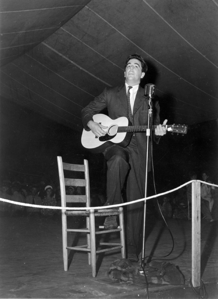 Alan Lomax playing guitar on stage at the Mountain Music Festival, Asheville, N.C.