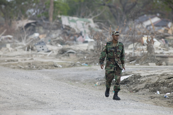 After Hurricane Katrina, a National Guardsman walks through a residential area that was reduced to debris.