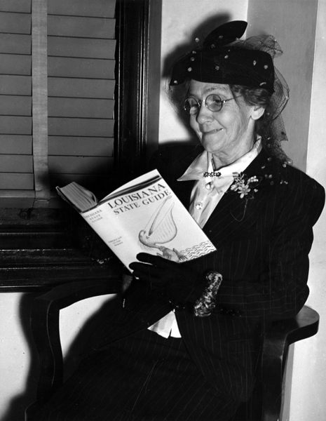 """Elderly woman reading the Louisiana State Guide in the 1930s"""