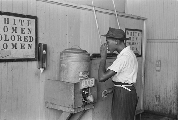 Young man drinking from segregated water cooler