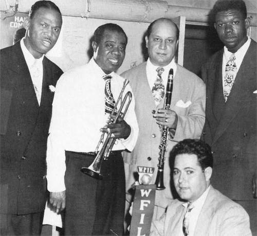 Al Rose, at the microphone, poses with (from left) Earl Hines, Louis Armstong, Barney Bigard and Arvel Shaw at Philadelphia's Academy of Music in 1947.