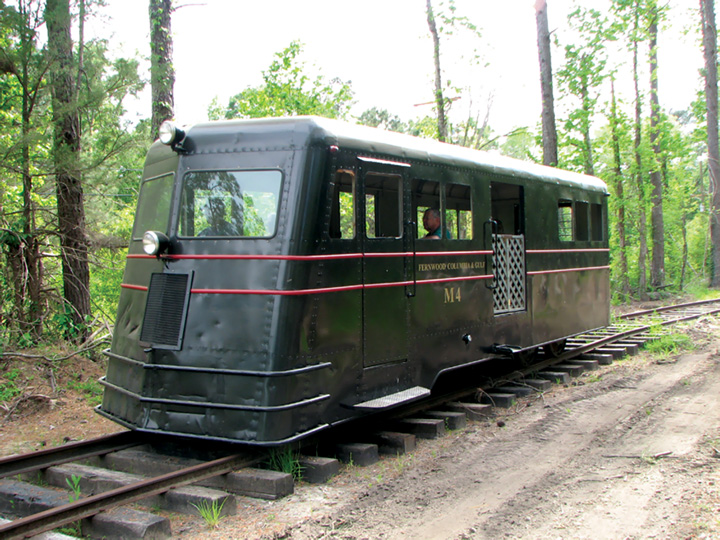 An M4 passenger railroad car carries visitors on a circle track around the Southern Forest Heritage Museum. Vehicles of this type were formerly used to transport workers from mills to logging sites. Photo by Jason Rose.