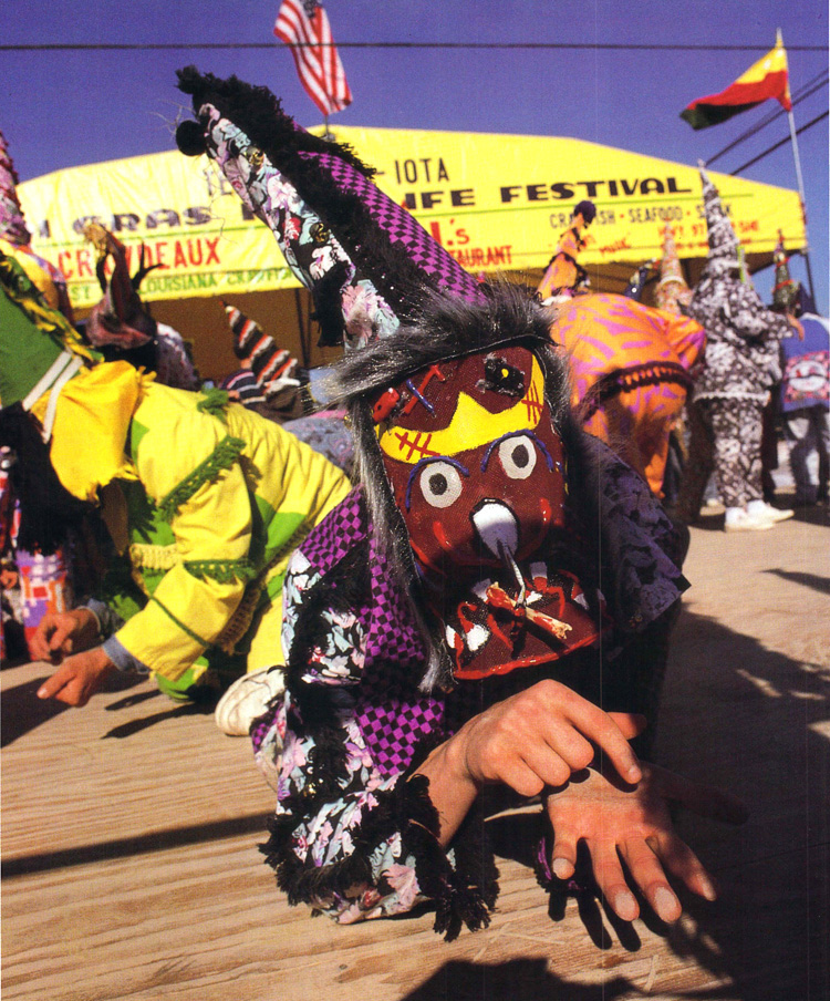 """A masker imitates the Mardi Gras run gesture of supplication at the """"Tee"""" Mamou-Iota Folklife Festival. Such fairs have kept tourists occupied in the cities while locals make their traditional gumbo run in the countryside with as little outside interference as possible. Photo by Phillip Gould"""