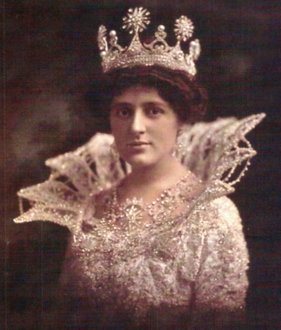 Queen of Proteus in 1912, Corinne McCloskey wears a delicate Medici-style collar with her white lace dress and crown jewels.