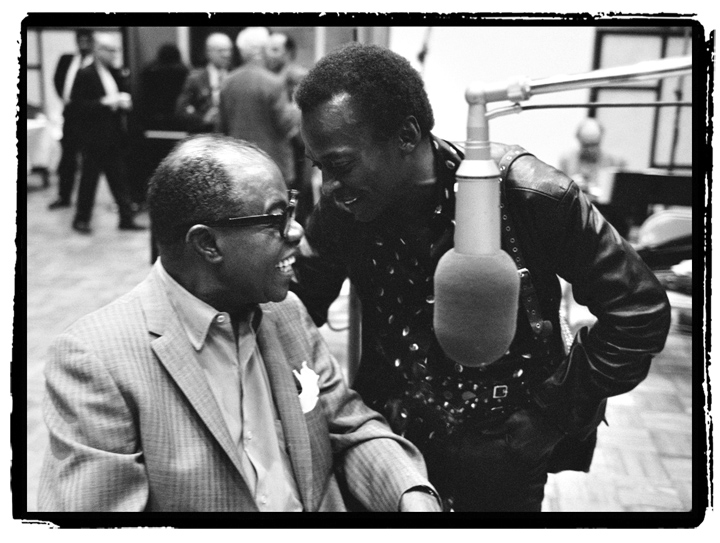 This photo of Louis Armstrong and Miles Davis was taken during the May 25, 1970 recording session for the album, Louis Armstrong and His Friends?. The session celebrated ArmstrongÕs upcoming 70th birthday and several notable guests stopped by for the celebration, including Tony Bennett, Ornette Coleman, Bobby Hackett and many more. Photo by Jack Bradley, Courtesy of the Louis Armstrong House Museum