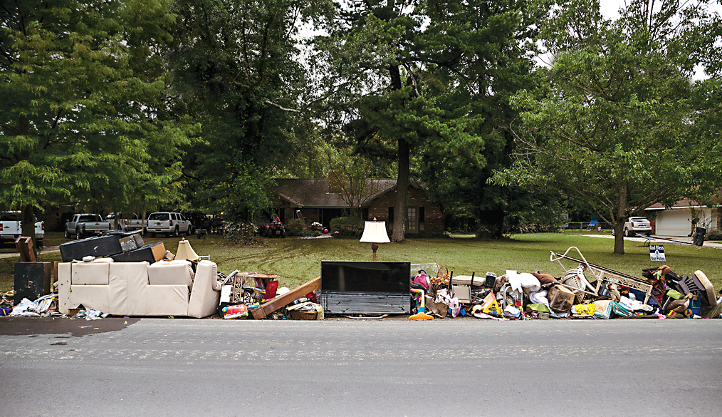 The belongings of the Bridges family gathered on the sidewalk outside their home in Denham Springs. Photo by Bryan Tarnowski